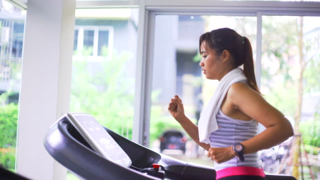 asian woman running on a treadmill - coda di cavallo video stock e b–roll