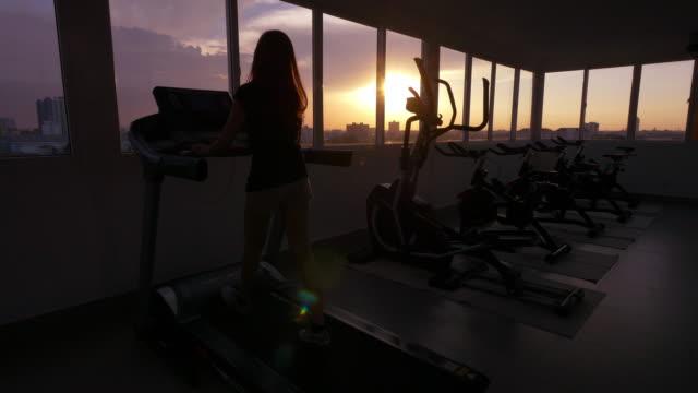 vídeos de stock, filmes e b-roll de mulher asiática corridas em uma esteira - esteira rolante aparelho de musculação