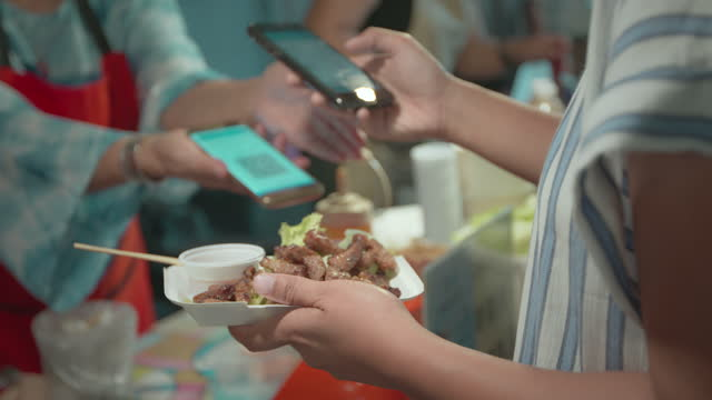 asian woman scan barcode to make payment from smartphone after bought grilled pork in night market street food. street food in thailand. - equipment stock videos & royalty-free footage