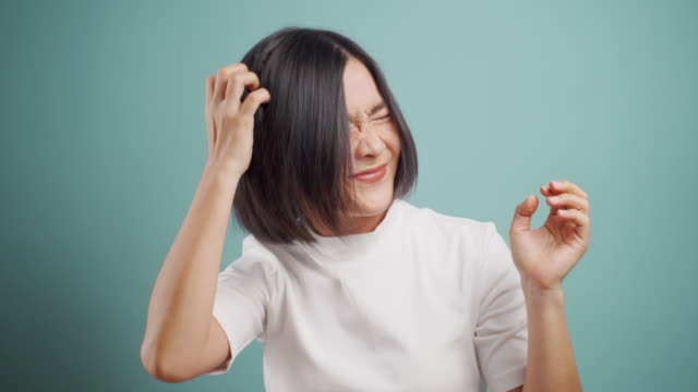 asian woman  scratching her head and standing isolated over blue background. health care concepts. 4k video. - plain background stock videos & royalty-free footage