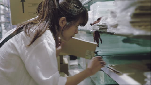 asian woman searching for a book in a bookstore - librarian stock videos & royalty-free footage