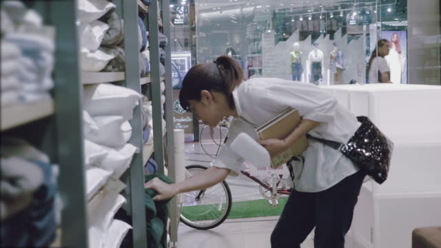 asian woman searching for a towels and blanket in a supermarket. - adult diaper stock videos and b-roll footage