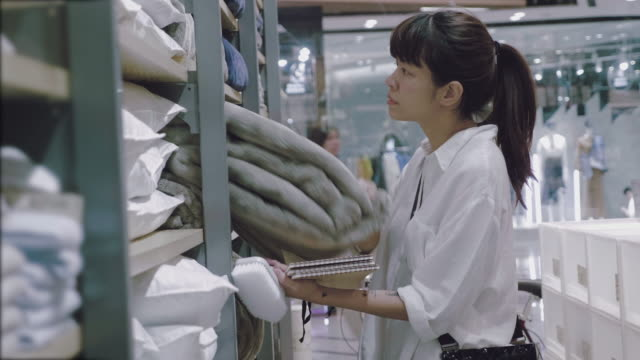 Asian woman searching for a towels and blanket in a supermarket.