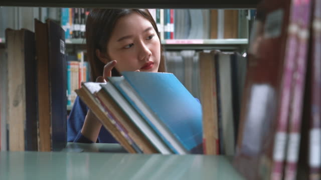 asian woman searching the book in library - book shop stock videos & royalty-free footage