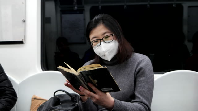 asian woman seating in subway train wearing pollution mask / beijing, china - pollution mask stock videos and b-roll footage