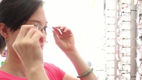 stockvideo's en b-roll-footage met aziatische vrouw select bril - bril brillen en lenzen