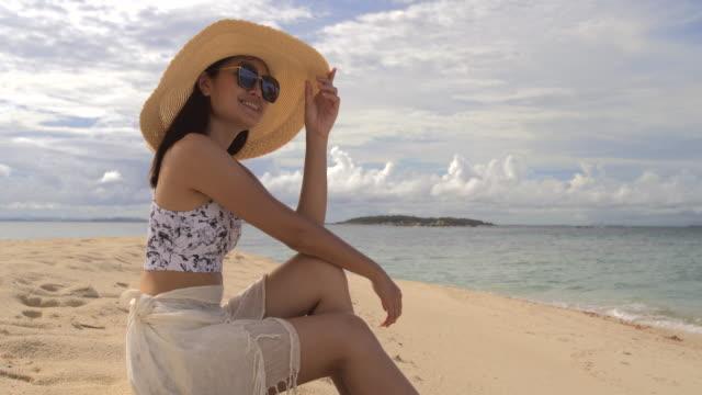 vídeos y material grabado en eventos de stock de mujer asiática se sienta en la arena de la playa. - brazo humano