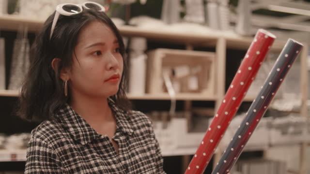vidéos et rushes de femme asiatique shopping au marché de noël. - objet en papier