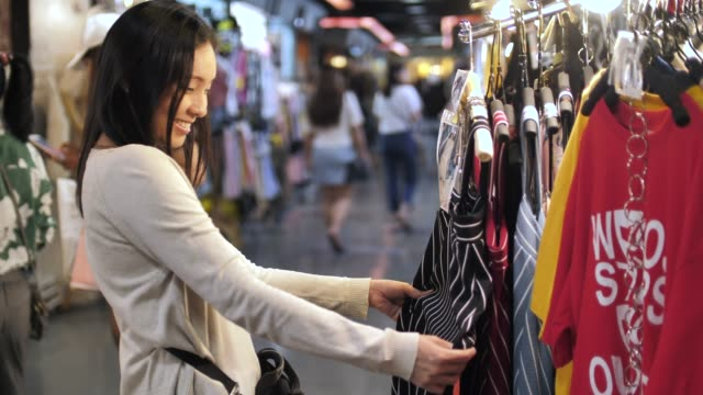 asian woman shopping clothes at street market - clothing store stock videos and b-roll footage