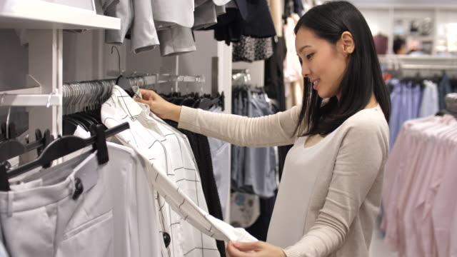 vídeos de stock, filmes e b-roll de mulher asiática, compras de roupas na loja de roupas - comércio consumismo