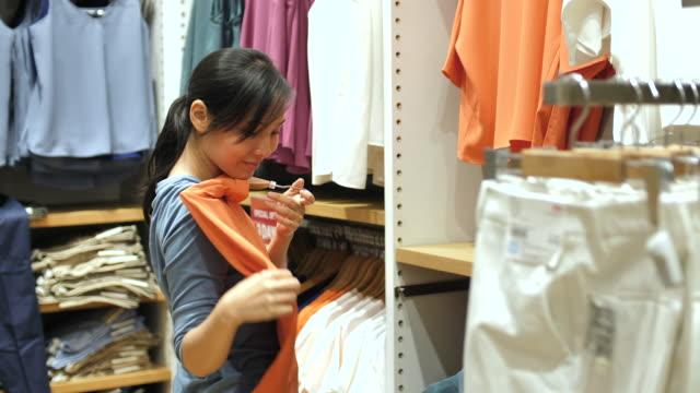 vídeos de stock, filmes e b-roll de mulher asiática comprando roupas no shopping center - top