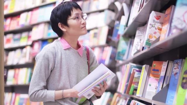 ショッピングモールで本を買うアジアの女性 - 見つける点の映像素材/bロール