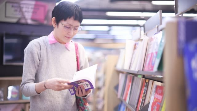 asian woman shopping for book at shopping mall - book shop stock videos & royalty-free footage