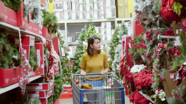 asian woman shopping for christmas at the supermarket - merchandise stock videos & royalty-free footage