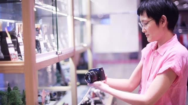 ショッピングモールでデジタルカメラを買うアジアの女性 - カメラ点の映像素材/bロール