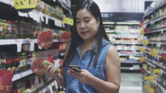 asian woman shopping in a grocery store,4k slo mo - nutrition label stock videos and b-roll footage