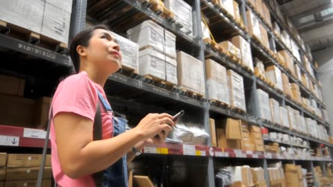 asian woman shopping in modern warehouse, slow motion. - electronic organizer stock videos & royalty-free footage