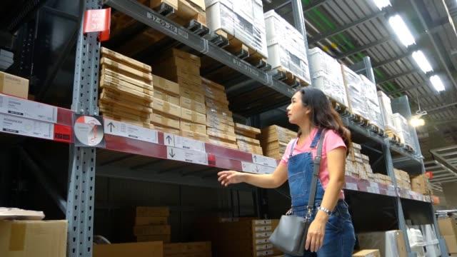アジアの女性は近代的な倉庫で買い物、スローモーション。 - メガストア点の映像素材/bロール