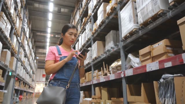 asian woman shopping in modern warehouse, slow motion. - electronic organiser stock videos & royalty-free footage