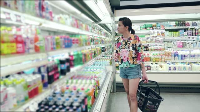 stockvideo's en b-roll-footage met aziatische vrouw winkelen in de supermarkt - dairy product