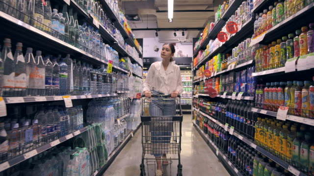 asian woman shopping in supermarket - cibi surgelati video stock e b–roll