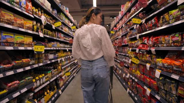 vídeos de stock, filmes e b-roll de mulher asiática fazendo compras em supermercado - orgânico