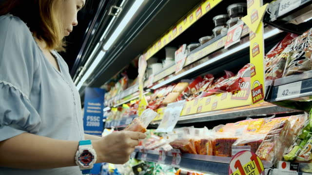 donna asiatica che fa shopping al supermercato - cibi surgelati video stock e b–roll