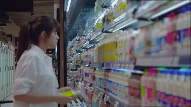 アジアの女性スーパー マーケットでショッピング
