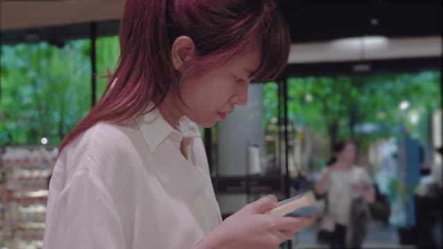 アジアの女性スーパー マーケットでショッピング - ビニール袋点の映像素材/bロール