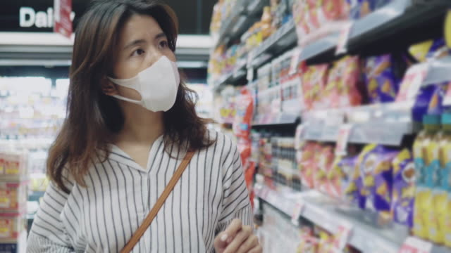 asian woman shopping in supermarket with face mask protection - mask disguise stock videos & royalty-free footage