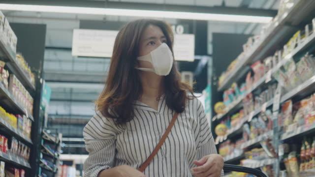 vídeos de stock, filmes e b-roll de mulher asiática fazendo compras em supermercado com proteção contra máscaras faciais - máscara