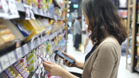 vídeos y material grabado en eventos de stock de mujer asiática de compras en el supermercado con smart phone, cámara lenta - gran almacén