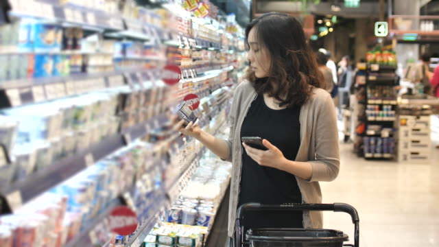 asian woman shopping in supermarket with smart phone, slow motion - comprare video stock e b–roll