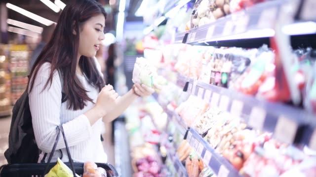 vídeos y material grabado en eventos de stock de mujer asiática comprando productos lácteos en supermercado - etiqueta
