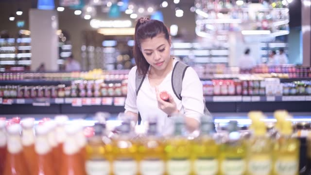 asian woman shopping on dairy product in supermarket - label stock videos & royalty-free footage