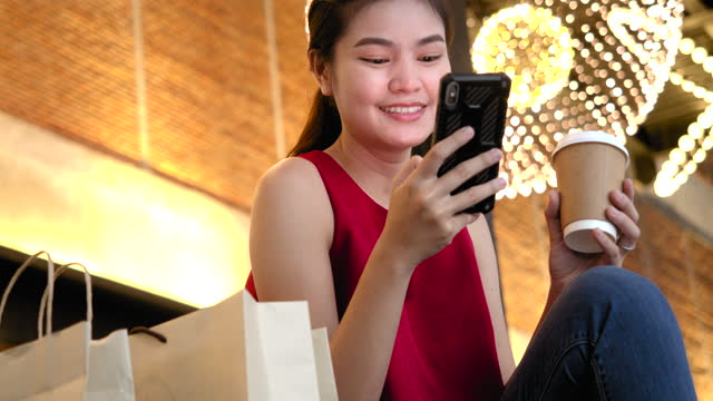 stockvideo's en b-roll-footage met aziatische vrouw die op mobiele telefoon met creditcard winkelt - cadeau
