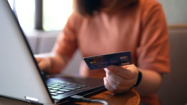 donna asiatica che fa shopping online e tiene la carta di credito della banca per il pagamento - oggetto creato dall'uomo video stock e b–roll