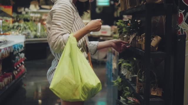 プラスチックフリー食料品袋とアジアの女性の買い物。 - レジ係点の映像素材/bロール