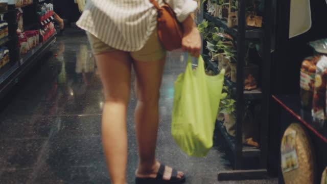 vidéos et rushes de femme asiatique faisant des emplettes avec les sacs d'épicerie libres en plastique. - sachet en papier