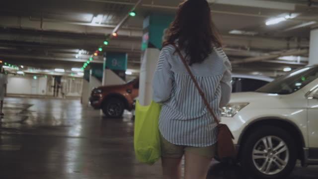 asiatische frau einkaufen mit kunststoff kostenlos lebensmitteltaschen. - parking stock-videos und b-roll-filmmaterial