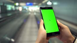 4K, Asian woman show the green screen phone on moving sidewalk at airport