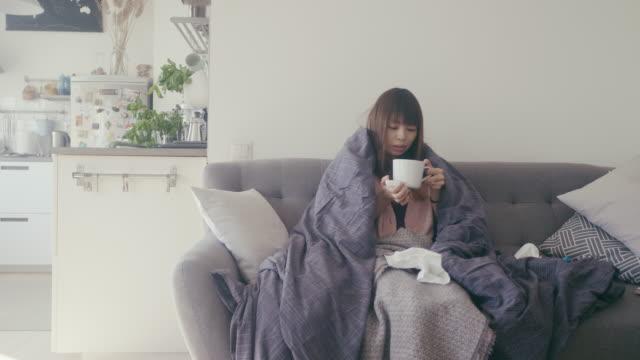 アジアの女性は自宅で病気で、熱い飲み物を飲む - カップ点の映像素材/bロール
