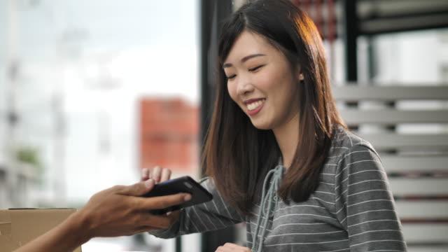 配達人から小包箱を受け取るスマートフォンに署名するアジアの女性、宅配 - 署名する点の映像素材/bロール