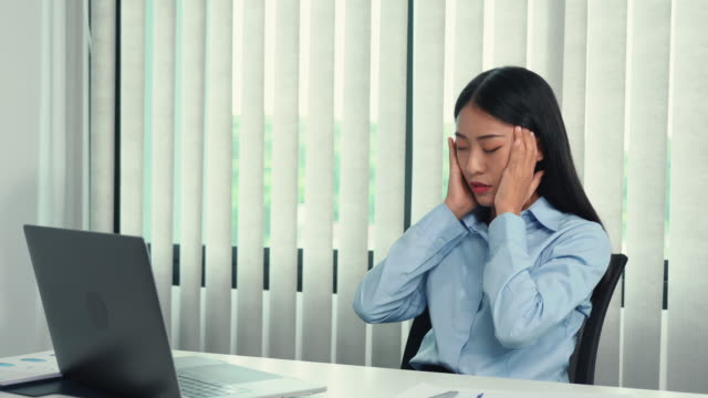 asian woman sitting at work caused a headache so she gently rubbed her head with her hand. - mental burnout stock videos & royalty-free footage
