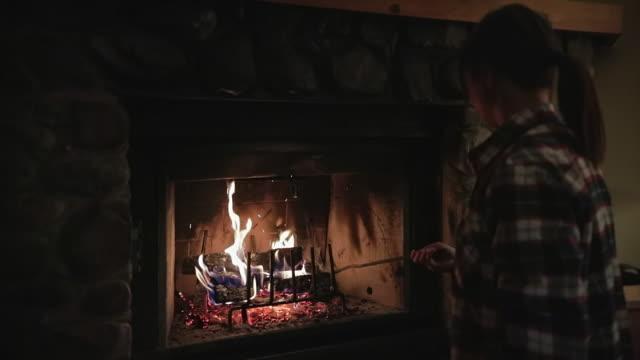 vídeos de stock e filmes b-roll de asian woman sitting by fireplace in a cabin in winter - cabana de madeira