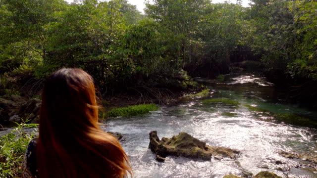 Asiatische Frau sitzt in der Nähe von See