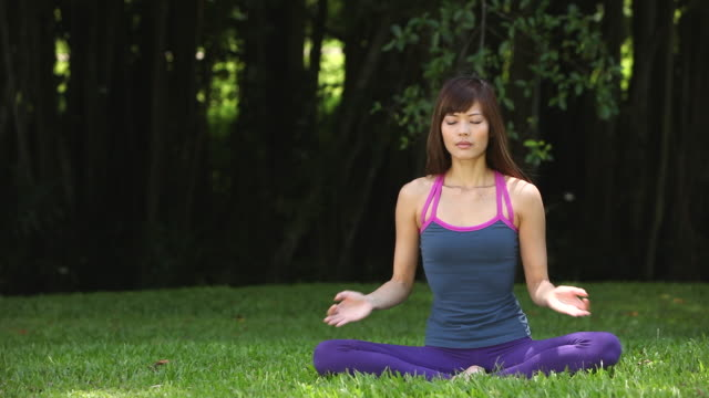 MS Asian woman sitting on grass in lotus position practicing Yoga