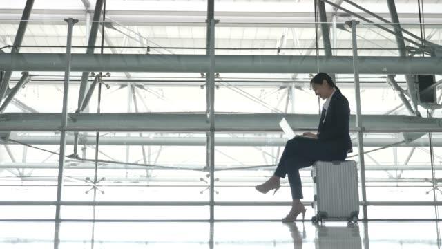asiatische frau sitzt im gepäck und arbeitet am laptop im flughafen - sitzen stock-videos und b-roll-filmmaterial