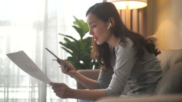 asian woman sitting on sofa and having video call meeting at home - headset stock videos & royalty-free footage