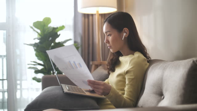 asian woman sitting on sofa and using laptop at home - research stock videos & royalty-free footage